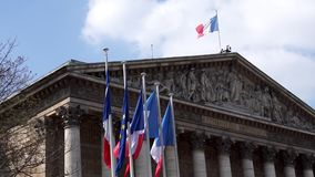 French and European flags in the wind in front of National Assembly stock footage