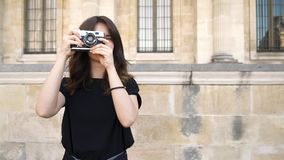 PARIS, FRANCE Pretty woman making photo with a film camera. Old buildings in Paris on background. PARIS, FRANCE Gimbal shot of pretty smiling caucasian brunette stock video footage