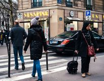 French male and female crossing street in front of Mercedes -Ben. PARIS, FRANCE - JAN 30, 2018: French male and female crossing street in front of Mercedes -Benz Royalty Free Stock Photo