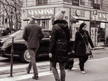 French male and female crossing street in front of Mercedes -Ben. PARIS, FRANCE - JAN 30, 2018: French male and female crossing street in front of Mercedes -Benz Royalty Free Stock Image