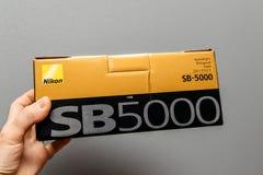 Nikon SB-5000 Speedlight featuring Radio Control Advanced Wirele. PARIS, FRANCE - JAN 23, 2018: Man holding against gray background a box of Nikon SB-5000 Royalty Free Stock Photos