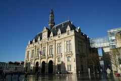 Mairie de Saint Denis or city hall of Saint Denis and Place Victor Hugo after the shower. Paris,France-January 19,2018: City hall of Saint Denis is situated at Royalty Free Stock Photo
