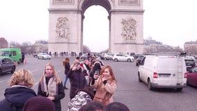 PARIS, FRANCE - JANUARY, 1, 2017. International tourists making photos near famous triumphal arch, Arc de Triomphe Stock Photo
