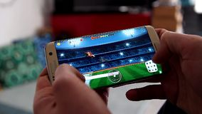 Prime peaks racing game. Paris, France, January 17, 2018: man playing prime peaks a25 apps racing video game on his modern smartphone Samsung Galaxy S7 Edge At stock footage