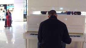 PARIS, FRANCE - JANUARY, 1, 2017 Steadicam shot man playing piano in duty free stores area at the airport. 4K video