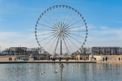 Paris ferris-wheel against blue sky from the Tuileries park with Royalty Free Stock Image