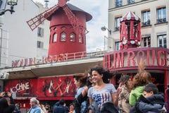 PARIS, FRANCE - 8 JUIN 2014 : Touristes posant devant le Moulin rouge, un des cabarets de Pigalle les plus célèbres image libre de droits