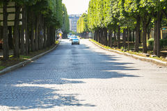 Paris, France - Jul 14, 2014: large paved tree-lined road with n Royalty Free Stock Photography