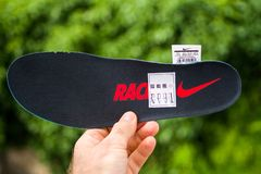 Man hand holding NIke Running shoes sole Racing logotype royalty free stock image