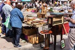 People choosing used books at the flea Aligre Market. Paris, Fra. Paris, France - Jule 09, 2017: People choosing rare and used books, vintage goods at the Stock Image