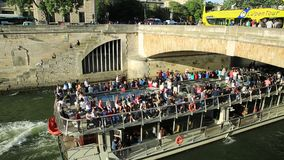 Cruise on Seine river. Paris, France - July 1, 2017: Bateaux-Mouches with many tourist during a trip on the River Seine passes under Pont Saint Michel. Cathedral stock footage