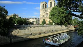 Cruise on Seine river. Paris, France - July 1, 2017: Bateaux-Mouches with many tourist during a trip at sunset on River Seine with Cathedral of Notre Dame on the stock video footage