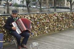 PARIS, FRANCE, 12 JULY, 2014- Elderly busker on Pont de Arts. An elderly Parisienne busker playing the piano accordian on the pedestrian bridge Pont de Arts Royalty Free Stock Images