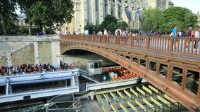 Cruise on Seine river. Paris, France - July 1, 2017: empty Bateaux-Mouches docked on the Seine under the red bridge with Notre Dame Cathedral on the Ile de la stock video footage