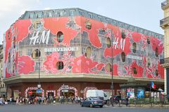 HM store building with people red floral decoration facade in Paris royalty free stock images
