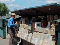 Riverside bookseller at an open-air bookshop in Paris. PARIS, FRANCE - JULY 3, 2018: A man stands in front of books displayed at an open-air bookshop locally stock photography