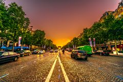 Champs Elysees Sunset. Paris, France - July 2, 2017: perspective view of Champs Elysees with Arc de Triomphe in the distance in a orange sunset sky with road royalty free stock photo