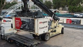 A reach stacker handles a container. PARIS, FRANCE - JULY 5, 2018: A reach stacker handles a container at a small port on the river Seine on July 5, 2018 in stock video footage