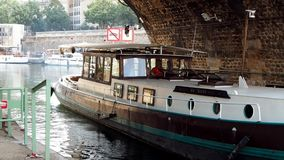 Skilled skipper steers a houseboat off Port de l`Arsenal in Paris. PARIS, FRANCE - JULY 13, 2018: A skilled skipper steers a houseboat off Port de l`Arsenal on stock footage