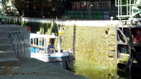 Small canal boat Ariane in Paris. PARIS, FRANCE - JULY 2, 2018: Small canal boat Ariane leaves a lock in the 10th arrondissement on July 2, 2018 in Paris, France stock video footage