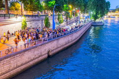 PARIS, FRANCE - JULY 21, 2014: Tourists walk along Seine River o Royalty Free Stock Photography