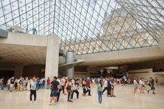 Visitors inside the Louvre Museum in Paris. PARIS,FRANCE - JULY 31,2017 : Visitors below the famous glass pyramid of the Louvre Museum in Paris Stock Photos