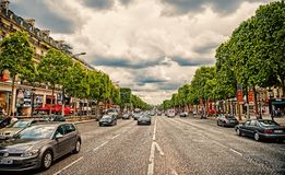 Paris, France - June 02, 2017: Avenue des Champs Elysees with busy traffic. Elysian fields road on cloudy sky. Vacation. And travel in french capital stock photo