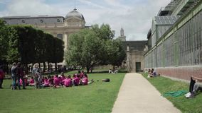 Openair lesson for elementary school children, Botanical garden near greenhouse. Paris, France- June 7, 2018: Jardin de Plantes - main botanical garden. The stock video