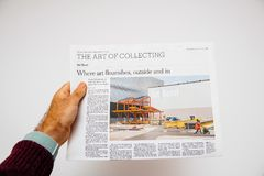 An holding newspaper The New York Times newspaper about Art Base. PARIS, FRANCE - JUNE 13, 2018: Man holding newspaper The New York Times newspaper about Art royalty free stock image