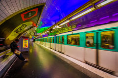 Paris, France - June 1, 2015: Metropolitain subway metro station, train rapidly passing by platform with cool neon Royalty Free Stock Photo