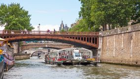 Pleasure Boat on the Seine in Paris. PARIS, FRANCE - JUNE 8, 2012: A modern pleasure boat, laden with tourists, passing under a bridge on the River Seine in Royalty Free Stock Images