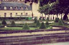 Paris, France June 1, 2015: Park area with cone shaped trees and an old building in the background Stock Images
