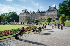 PARIS, FRANCE - JUNE 26, 2016: People relax and hang out in pucturesque park in front of Palais du Luxembourg or Luxemburg Palace. On bright summer sunny day stock images