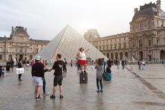 PARIS, FRANCE - June 01, 2018: tourists taking selfie photos in front of the Louvre Pyramid royalty free stock photo