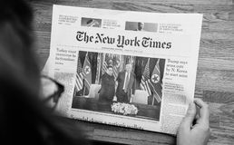 The New York Times about Trump Kim meeting summet singapore. PARIS, FRANCE - JUNE 13, 2018: Woman reading The New York Times newspaper in the office showing on royalty free stock photography