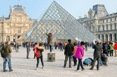 PARIS, FRANCE, LOUVRE. PARIS, FRANCE, people be photographed  in front of the Louvre palace and Louvre pyramid Stock Photography