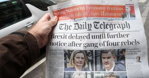 Brexit Delay front cover newspaper POV man buying The Daily Telegraph. Paris, France - Mar 15, 2019: Brexit delayed until further notice after gang of four stock footage