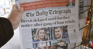 Brexit Delay front cover newspaper POV man buying. Paris, France - Mar 15, 2019: Brexit delayed until further notice after gang of four rebels the Daily stock footage