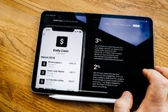 Daily Cash explanation man reading on tablet about Apple Card. Paris, France - Mar 27, 2019: Man POV at iPad Pro tablet reading on Apple.com website about new royalty free stock images