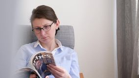 Tilt to woman reading magazine Forbes stock video footage