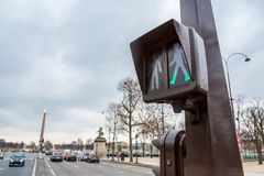 Green to Cross. Paris, France - March 22, 2015: A crossing signal illuminated in green tells pedestrians it is okay to crros the street stock photos