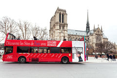 Red sightseeing bus and Paris Notre Dame Stock Photos