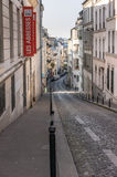 Paris, France, March 26, 2017: View on narrow cobbled street among traditional parisian buildings in Paris, France. Royalty Free Stock Photography