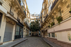 Paris, France, March 26, 2017: View on narrow cobbled street among traditional parisian buildings in Paris, France. Royalty Free Stock Image