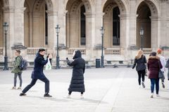 Paris, France. 29 March, 2018. Young man taking photo of his girlfriend near Louvre museum royalty free stock images
