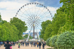 Paris, France - May 2, 2017: The Big Wheel at Place de la Concor. De view from Tuileries Garden with the crowd and cloudy sky in evening on May 02, 2017, in Royalty Free Stock Photos