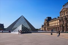 Famous glass pyramid in The Louvre on a bright sunny spring day. Famous touristic place and travel destination in Europe. Paris, France-MAY 06, 2018: Famous stock photography