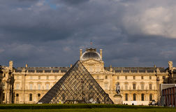 Paris, France May 26, 2015 The Louvre. The Louvre from the front with sunlight in late afternoon and a thunderstorm in the background Stock Images