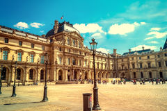 Paris, France - MAY 27, 2015: The Louvre in Paris on a sunny day. Old retro style. Paris, France - MAY 27, 2015: The Louvre in Paris on a sunny day with blue royalty free stock photo