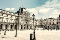 Paris, France - MAY 27, 2015: The Louvre in Paris on a sunny day. Old retro style. Paris, France - MAY 27, 2015: The Louvre in Paris on a sunny day with blue royalty free stock image